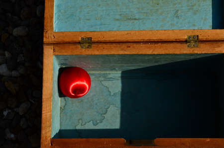 A wooden box with a red shining bullet, christmas bauble in it.
