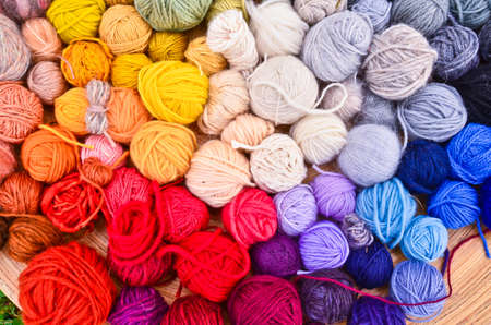 Close up picture of many colorful and vibrant balls, ravels of wool, laying in a large wooden bowl standing on the ground of green grass Stockfoto