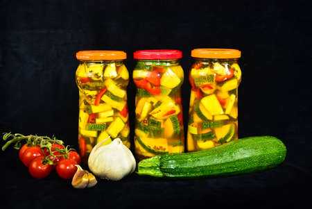 A still life of three glasses of pickled zucchini with some accessories arround and a black background