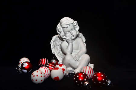 A small white angel sitting between red and white Christmas baubles, dreaming in front of black background Stock fotó