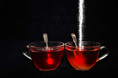 White sugar is rippling into one of two cups of tea in a glass, in front of black background
