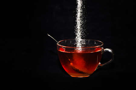 White sugar is rippling into a cup of tea in a glass, in front of black background