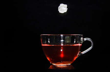 A piece of rock sugar is splashing into a glass cup of tea in front of a black background Banco de Imagens