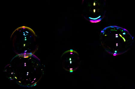 Beautiful bubbles of soap in front of black background, bright and glossy