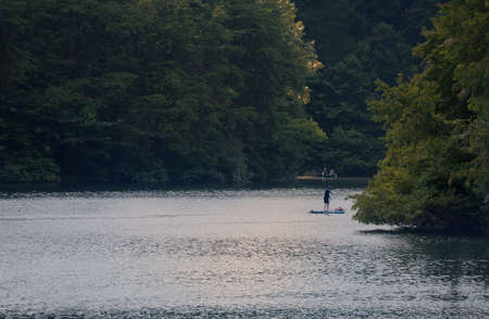 A summer afternoon on a mountain lake with a paddler on a paddle board and two men fishing in a small boat in the background.