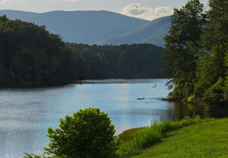 A paddler on a paddleboard enjoys a summer afternoon on a pristine lake in the Blue Ridge Mountains.