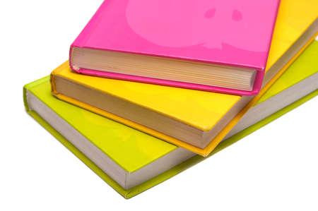 Magenta, yellow & green books on white background