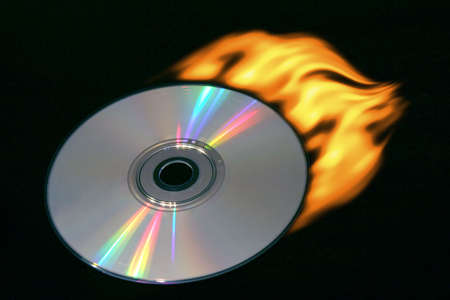 Compact disc with a tail of fire on a black background