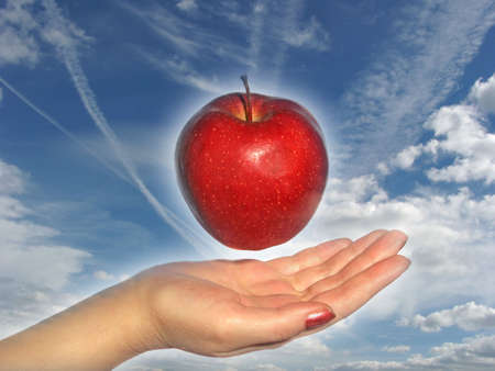 Apple above a hand on a sky background Stock Photo