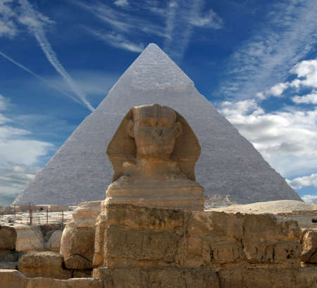 Sphynx and pyramid on a background of the cloudy sky Stock Photo
