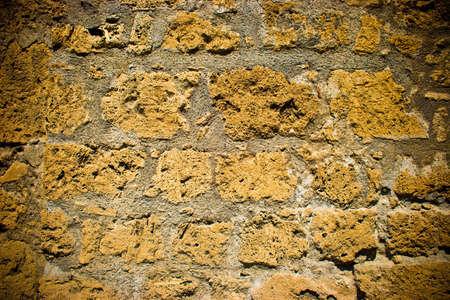 Old yellow brick wall with dark corners for design background Standard-Bild