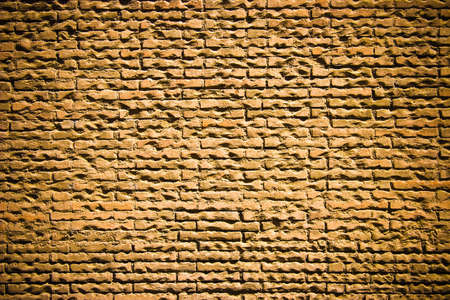 Old yellow brick wall with dark corners for design background Stock Photo