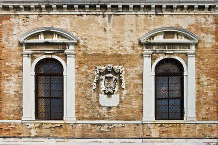 Old wall with windows and skull in center Stock Photo