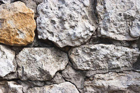 A stone wall with a rough texture.