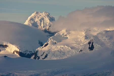 antarctic peninsula: Fog layers around the mountains on the Antarctic Peninsula in the first morning light Stock Photo