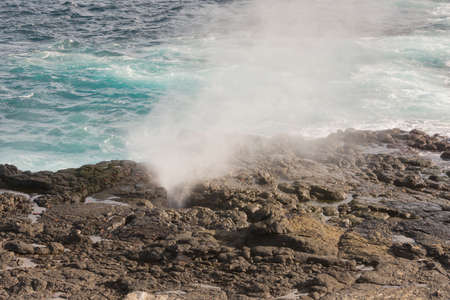 Blowhole on Espaola with sally lightfoot crabs, which appear as orange specs. The mist of the blowhole softens the focus. Stock Photo