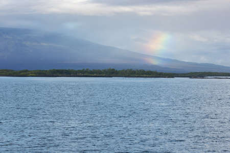 reduces: Rainbow over Isabela with shield volcano. Rain over land reduces the contrast