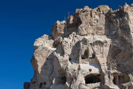 cave house: Uchisar Castle with turkish flag