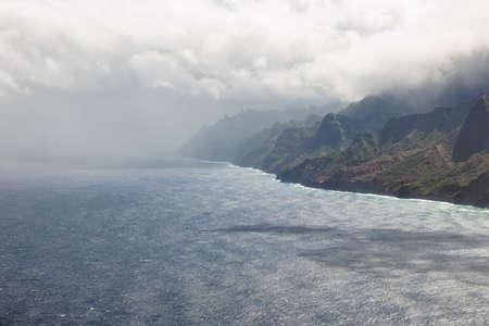 inhospitable: Rain storm over the Na Pali Coast on Kauai. Low clouds and dark shadows announce the storm Stock Photo
