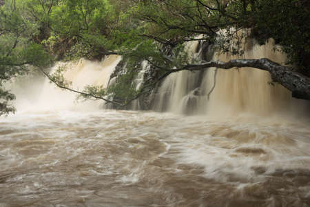 severely: Severely swollen Lower Twin Falls after a tropical rainstorm. The flash flood blocks the path to the Upper Twin Falls. Stock Photo
