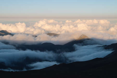 inhospitable: Warm and cold colors in the sunset over Haleakala with the cloud deck below the view point Stock Photo