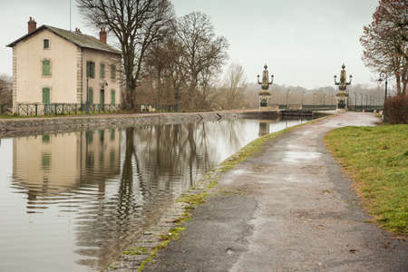 The Briare aqueduct with the lockkeepers house on a rainy day Stock Photo