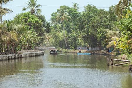 Hoofdartikel: ALAPPUZHA, KERALA, INDIA, 9 april, 2017 - Mens in een blauwe boot die mango's op de kust van een kanaal in Alappuzha oogsten, terwijl een woonboot voorbijgaat