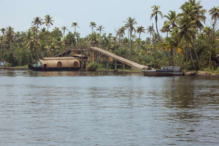 Housboat passing under a bridge over a canal in Alappuzha