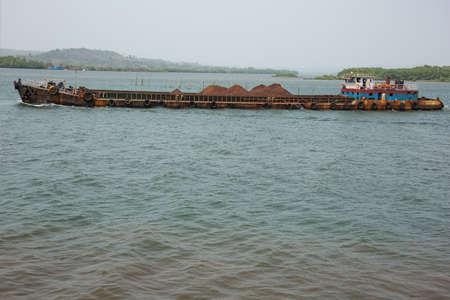 Rusty barge transporting iron ore on the Mandovi River Stock Photo