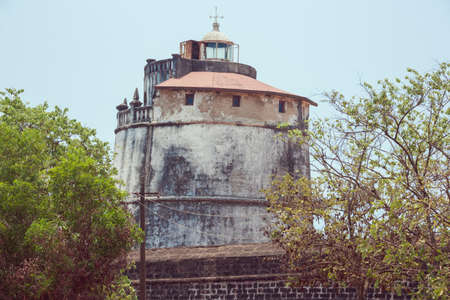 aguada: The lighthouse in Fort Aguada on the west coast of India emerging from behind the wall of the fort Stock Photo