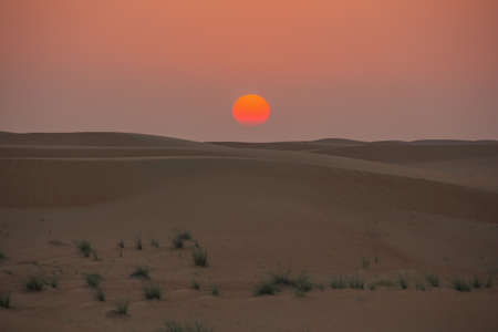 Sun almost touching the sand dunes in the Dubai desert Stock Photo