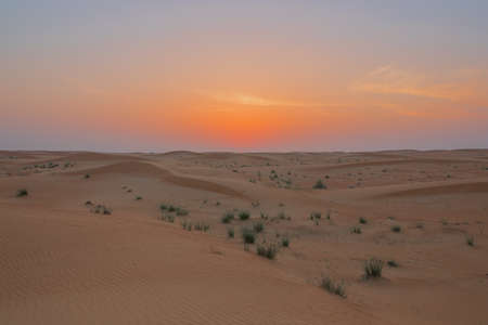 Sky bursting in colors when the sun touches the horizon in the Dubai desert Stock Photo
