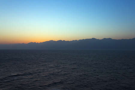 ridge of wave: Sunrise over the Gulf of Aqaba with the sun still behind the mountains Stock Photo