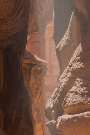khazneh: A first glimpse of the treasury, seen through the dusty mist hanging in the Siq Stock Photo