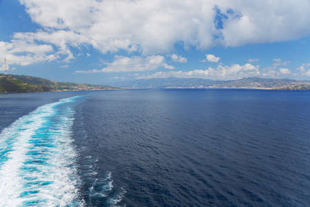 Navigating through the Strait of Messina with the mainland on the left and Sicily on the right