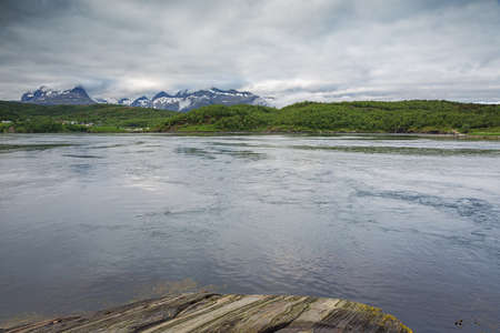 The Saltstraumen and distant mountains with the tidal current gushing through the channel