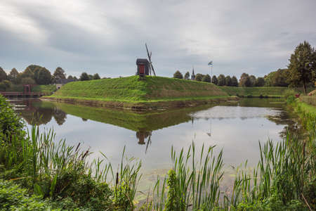 Looking at the fortified wall of Bourtange with the windmill in the background