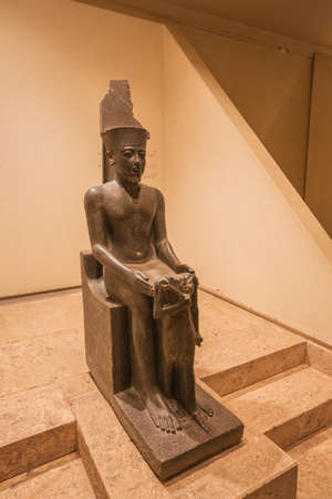 Editorial: LUXOR, EGYPT, October 16, 2018 - Horemheb sitting on a throne in the Luxor museum Редакционное