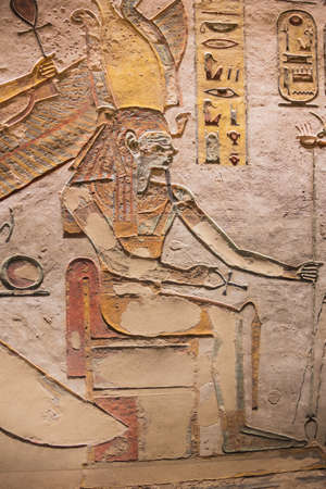 Painting of the divine pharaoh sitting on a throne in the tomb of Ramesses III