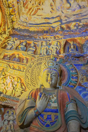 Weathered colorful Buddha with little statues in cave 9 of the Yungang Grottoes near Datong