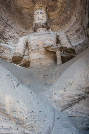 Large weatherworn Buddha statue in cave 17 of the Yungang Grottoes near Datong