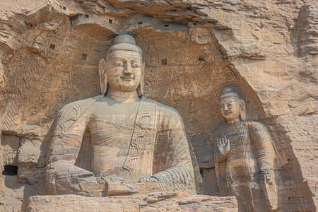 Close up of two Buddha statues in a niche in the Yungang Grottoes near Datong