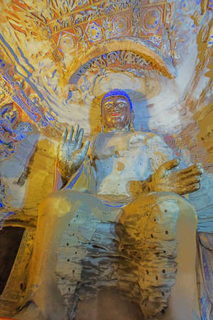 Weathered colorful Buddha statue in cave 9 of the Yungang Grottoes near Datong Stockfoto