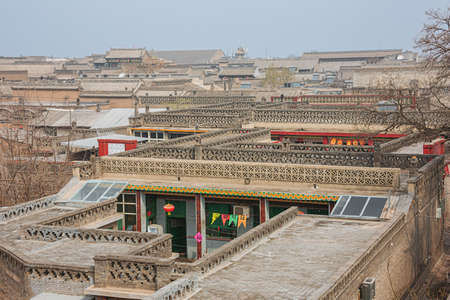 Walking past the tiled roofs in the old town of Pingyao seen from the city wall Фото со стока