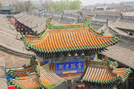 A colored tiled roof of a city gate in Pingyao seen from the city wall
