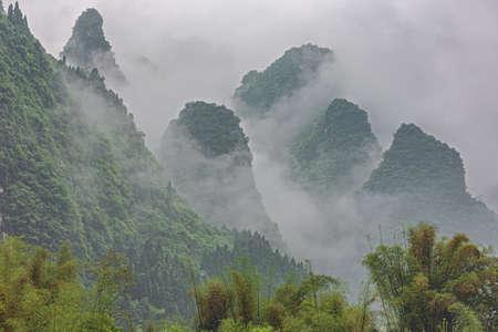 Dense clouds rising along the hills near Yangshuo on the Li River near Guilin 写真素材