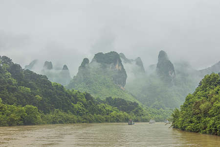 Hills bordering the Li River pointing through the clouds in the vicinity of Yangshuo near Guilin