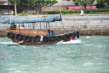 Editorial: HONG KONG, CHINA, April 22, 2019 - Passing a sampan in Aberdeen harbor in Hong Kong. Motion blur due to the speed of the sampan
