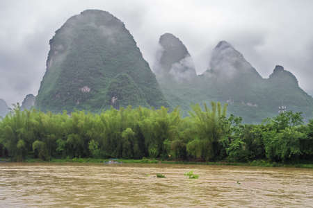 Small boat on the Li River valley while passing Xingpingzhen fishing village in the vicinity of Yangshuo near Guilin