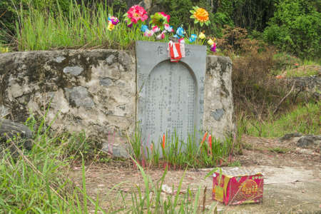Editorial: YANGSHUO, GUANGXI, CHINA, April 19, 2019 - Traditional grave in the middle of fields in the vicinity of Yangshuo near Guilin